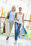 Friends shopping in mall. Carrying bags Royalty Free Stock Images