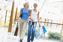 Friends shopping in mall. Carrying bags Royalty Free Stock Photo