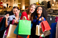 Friends shopping with presents in mall Stock Photo