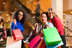 Friends shopping with presents in mall Stock Photography