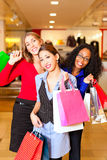 Friends shopping with presents in mall Stock Image