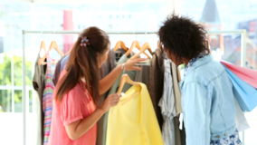 Friends shopping together and smiling at camera. In a clothing store stock video
