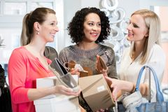 Friends on a shopping trip discussing sandals and buying shoes Royalty Free Stock Photography