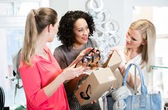 Friends on a shopping trip discussing sandals and shoes. Friends on a shopping trip discussing sandals and buying shoes royalty free stock image