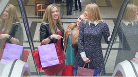 Friends shopping. Two beautiful young women taking. Escalator in shopping mall
