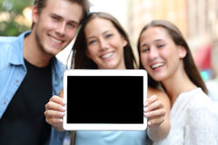 Friends showing a blank tablet screen. Three happy friends showing a blank tablet screen in the street Royalty Free Stock Photography