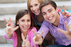 Friends showing peace sign. Portrait of young people smiling Royalty Free Stock Images