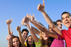 Friends showing thumb up. Happy group of joyful friends raising hands with thumb up sign against blue sky Stock Photos