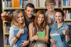 Friends showing thumb up in library Royalty Free Stock Image