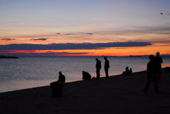 Friends in silhouette. Italy, Trieste. Friends at sunset near the sea Stock Images