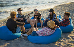 Friends singing guitar songs on the beach. They are sitting on bean bags. Friendship concept Royalty Free Stock Photography