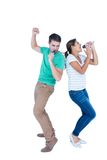 Friends singing in a microphone back to back Royalty Free Stock Photos
