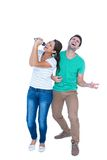 Friends singing in a microphone and playing air guitar Stock Images