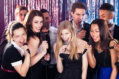 Friends singing into microphones at karaoke party Stock Photos