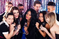 Friends singing into microphones at karaoke party Royalty Free Stock Photography
