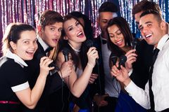 Friends singing into microphones at karaoke party Stock Images