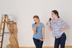 Friends singing into paintbrushes by ladder in a new house Stock Photography