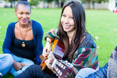 Friends singing songs in park having fun together Royalty Free Stock Images