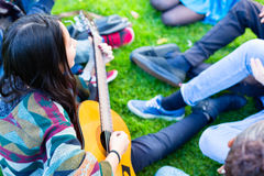 Friends singing songs in park having fun together. With one girl playing the guitar, diversity group of African, Asian and Caucasian people Stock Photo