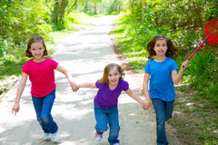 Friends and sister girls running in the forest track happy. Friends and sister girls running in the forest track smiling happy with butterfly net Royalty Free Stock Photos