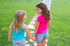 Friends sister girls together in grass track. Friends sister girls together in grass garden track holding hand looking eachother stock photo