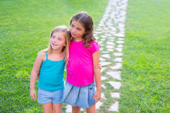 Friends sister girls together in grass track. Friends sister girls together in grass garden track hugging eachother royalty free stock photos