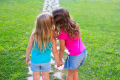 Friends sister girls whispering secret in ear. In grass garden track park outdoor royalty free stock photo