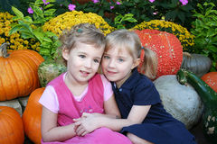 Friends and Sisters. Two little girls smile for the camera while sitting in front of some pumpkins and flowers Stock Images