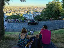 Friends sit on blanket and view skyline of Paris from Montmartre. Friends view Paris at sunset from the top of Montmartre, France Stock Photos