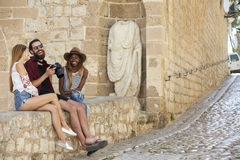 Friends sit looking at photos on a camera laughing, Ibiza Stock Photos
