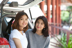 Friends sit in the open back of a car Stock Photography
