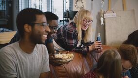 Friends sit together, watch funny movie on TV. Multi-ethnic group watching sports, discussing and chatting joyfully. stock video footage
