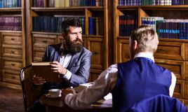 Friends sitting on armchairs in the library, vintage style. Oldfashined men with beard or hipster spend time together with friend in library, speaking or Stock Photography