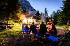 Friends sitting around bonfire in the woods and vacation house. Young people sitting around fire with mountain cottage and mountains in the background Royalty Free Stock Image