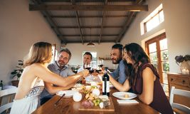 Friends having fun with wine and food at home party. Friends sitting around a table having fun with wine and food. Group of men and women toasting wine at dinner Stock Images