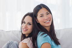 Friends sitting back to back smiling at camera Royalty Free Stock Photo