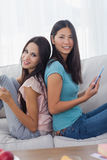 Friends sitting back to back with their tablets smiling at camer Royalty Free Stock Photography