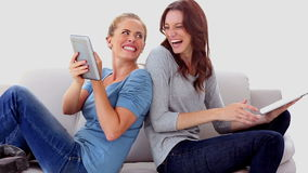 Friends sitting back-to-back using tablet pc. On the couch at home stock footage