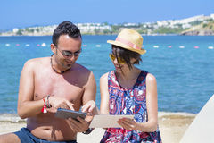 Friends sitting on the beach ,having fun with tablets Royalty Free Stock Image