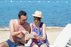 Friends sitting on the beach ,having fun with tablets Royalty Free Stock Photos