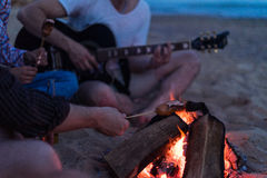 Friends sitting on the beach. man is playing guitar. Closeup view of young and cheerful friends sitting on beach and fry sasuages or weenies in bonfire One man Stock Images