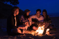 Friends sitting on the beach. man is playing guitar. Royalty Free Stock Images