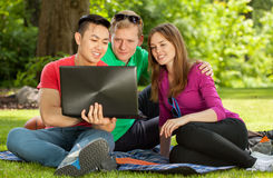 Friends sitting on blanket in park Stock Photo