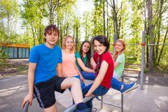 Friends sitting on brachiating at the playground Stock Image