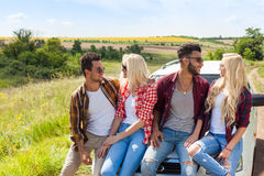 Friends sitting on car outdoor countryside people smile Stock Photos