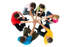 Friends sitting in a circle stacking hands Stock Photo