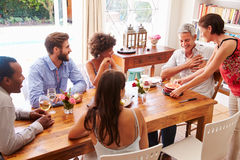 Friends sitting at a dining table celebrating a birthday Royalty Free Stock Image