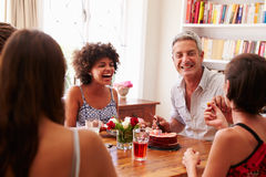 Friends sitting at a dining table laughing together Royalty Free Stock Photos