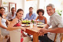 Friends sitting at a dining table, looking at camera Royalty Free Stock Photos