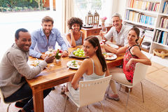 Friends sitting at a dining table looking at the camera Royalty Free Stock Photography